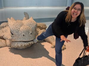 Picture of Ai with lizard statue chewing on her foot